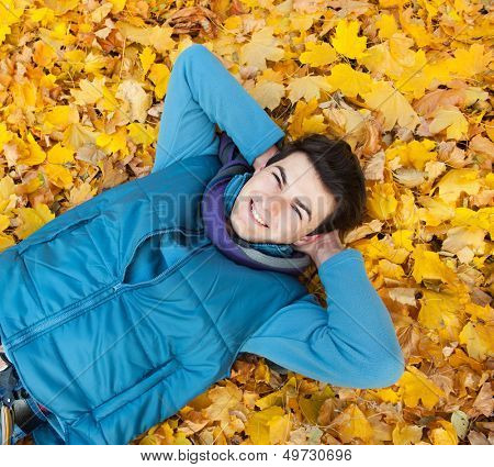 Young smiling man portrait laying in foliage. Autumn outdoor.