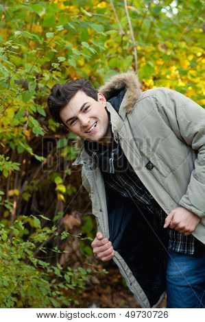 Young smiling man in park. Autumn autdoor.