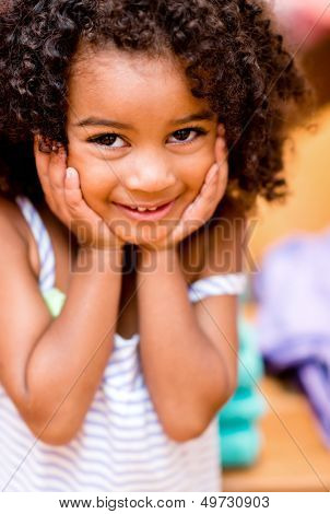 Portrait of a sweet little girl looking shy and smiling
