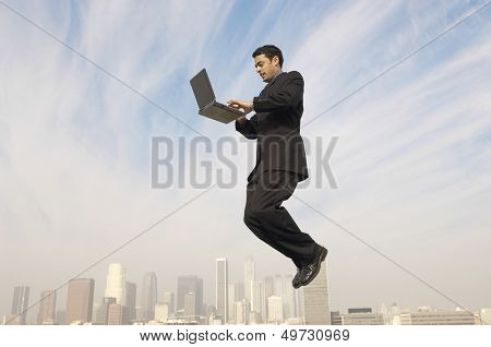 Full length side view of businessman using laptop in midair with cityscape in background