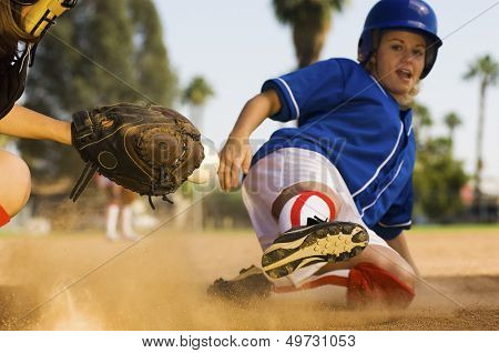 Full length of softball player sliding into home plate