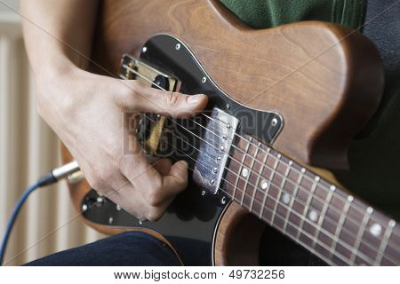 Closeup of a young man strumming chord on guitar