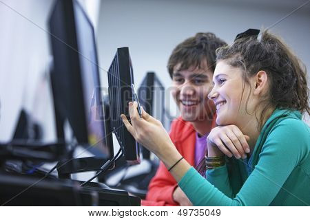 Side view of two young university students using computers