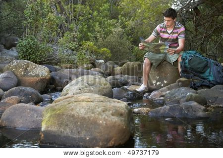 Teenage boy sitting on stone by river reading map