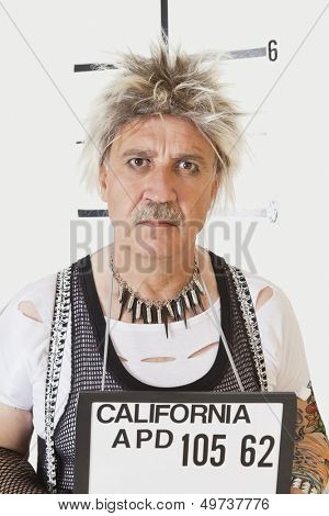 Mug shot of serious senior male punk