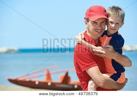 Lifeguard man with rescued child from drowning on a sea beach