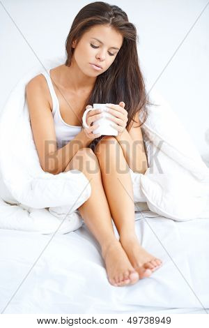 Woman drinking coffee in bed sitting in her pyjamas holding the mug cupped in her hands with a thoughtful downcast expression