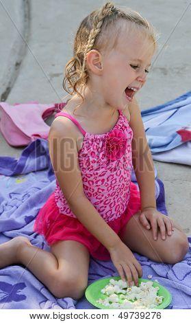 laughing female toddler eating popcorn