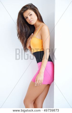 Sexy woman posing in mini skirt against white wall