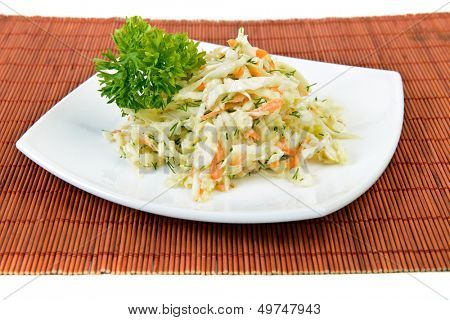 Dish of cabbage and carrot salad  (coleslaw) at restaurant over white