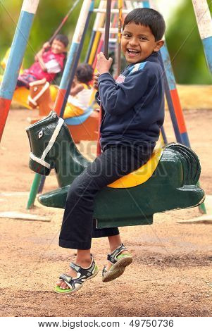 Happy Young Handsome Boy(kid) Playing On Swing Sets In A Park