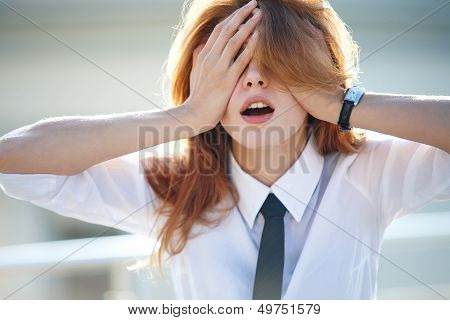 Delightful young woman closed her eyes with both hands