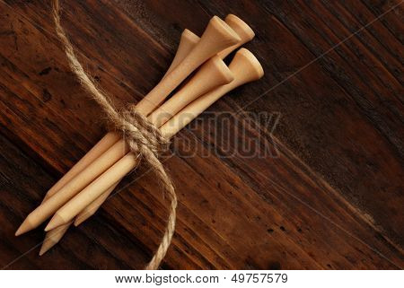 Natural colored wooden golf tees (tied with twine) on rustic, dark wood background with copy space.  Low key still life with directional, natural lighting for effect.