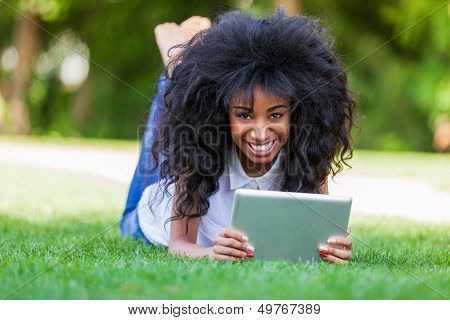 Outdoor Portrait Of A Teenage African American Girl Using A Tactile Tablet