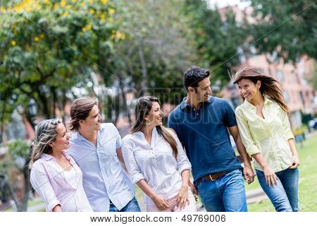 Group of friends walking at the park looking very happy