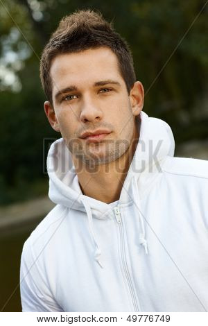 Outdoor portrait of young man in park, looking at camera.