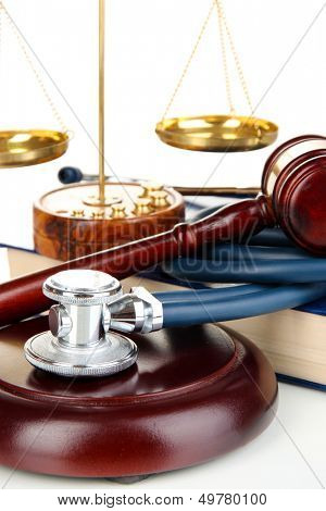 Medicine law concept. Gavel, scales and stethoscope on book close up