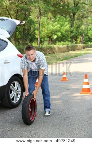 Man driver having trouble at road changing wheel