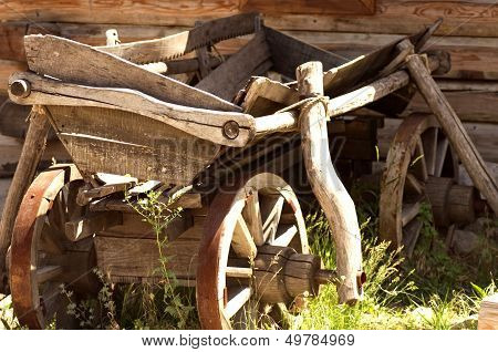 An ancient wooden cart is on a rural farmstead
