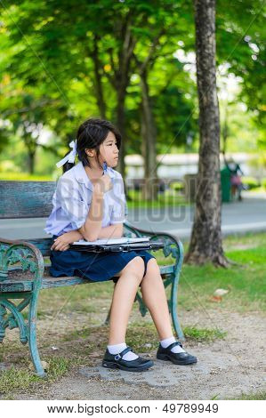Cute Thai Schoolgirl Is Sitting And Studying On A Bench