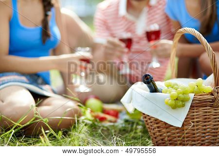 Basket with bottle and grapes on background of cheering friends
