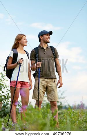 Couple of smiling trippers standing in the countryside at summer