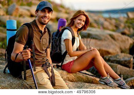 Handsome hiker looking at camera with his girlfriend on background