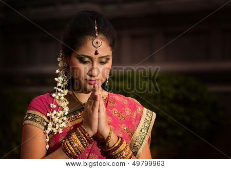 Portrait of beautiful young Indian woman in traditional sari dress praying in a hindu temple.