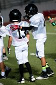 pic of huddle  - Young football boy putting his arm around his teamate.