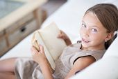 picture of 7-year-old  - Portrait of 7 years old child reading book on the sofa at home - JPG