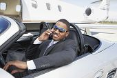 stock photo of jet  - Young businessman using cell phone in convertible near private jet - JPG