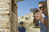 stock photo of shooting-range  - Man watching colleague aiming hand gun at firing range - JPG