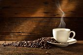 stock photo of breakfast  - Coffee cup and coffee beans on old wooden background - JPG