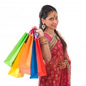 Portrait of beautiful young Indian woman in traditional sari dress shopping, standing isolated on wh