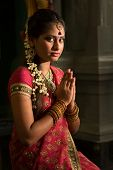 stock photo of sari  - Young Indian female in traditional sari dress praying in a hindu temple - JPG