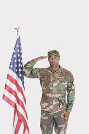 image of united states marine corps  - Portrait of US Marine Corps soldier saluting American flag over gray background - JPG