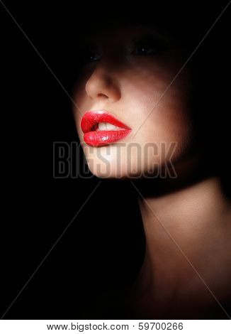 Darkness. Woman's Face With Sexy Red Lips In Spotlight And Shadows. Secrecy