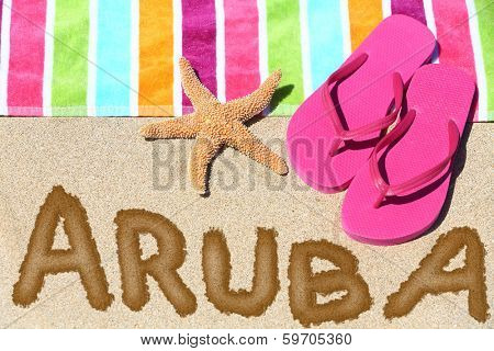 Aruba beach travel concept. ARUBA written in sand with water next to beach towel, summer sandals and starfish. Summer and sun vacation holidays.