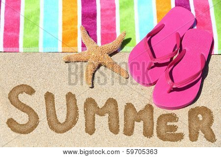 Summer vacation beach travel text concept. SUMMER written in sand with water next to beach towel, summer sandals and starfish.