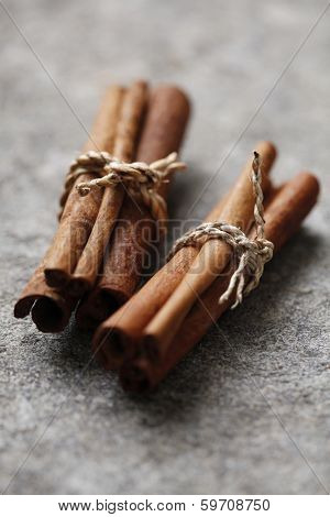 two bundles of cinnamon on a stone surface