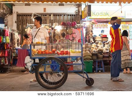 BANGKOK, THAILAND - JANUARY 9, 2012: Local man stands behind his street food cart on Khao San Road. Everyday thousands of tourists and locals buys food on these carts and stalls.