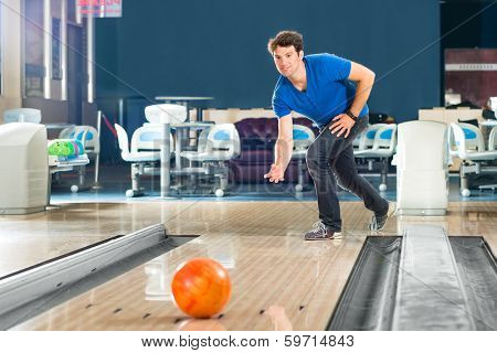 Group of friends in a bowling alley having fun, the girls cheering then he get a strike