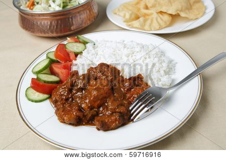 Chicken tikka masala  with basmati rice, a salad and poppadums