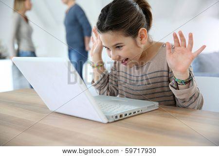 Young girl at home cwaving at laptop webcamera