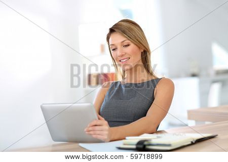 Businesswoman in office working on digital tablet