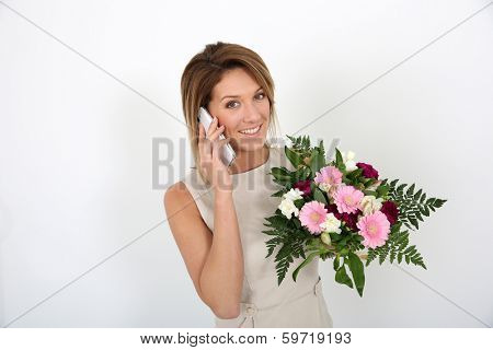 Beautiful woman with bunch of flowers making a call