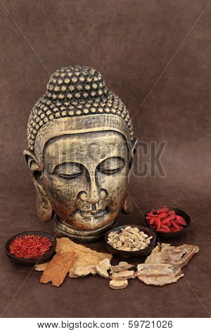Chinese herbal medicine selection with buddha head over handmade lokta paper background.