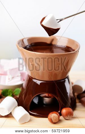 Chocolate fondue with marshmallow candies, on wooden table, on light background
