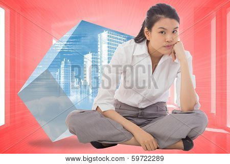 Grumpy businesswoman sitting cross legged against bright red room with windows