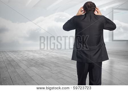 Stressed businessman with hands on head against room with holographic cloud
